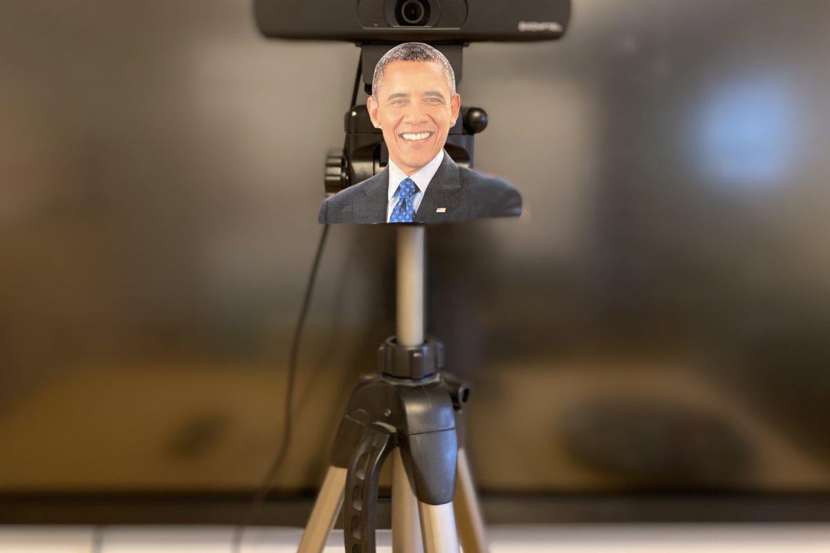 En kamera på stativ. Under kameralinsen finns en bild på en leende Barack Obama.